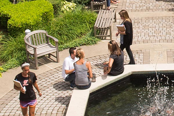 students hanging out by at the fountain in the Marian Hall Courtyard