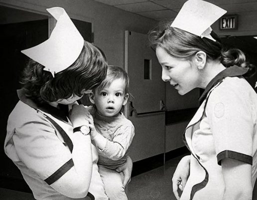 black and white photo of nurses holding a baby