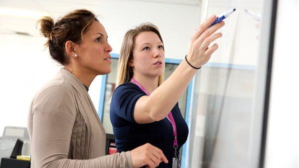 Jillian Mertzlufft helping a student at a white board