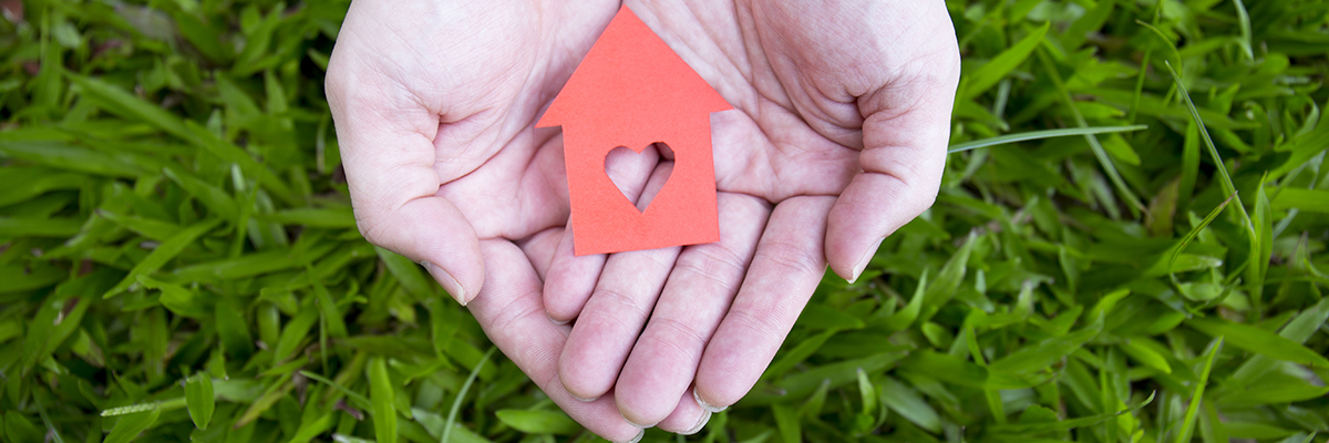 hands holding red paper house over green grass.
