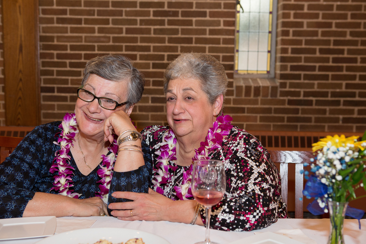 Class of 1967 50th Reunion two women wearing pink flower leis sitting at a table in Fitzgerald Court