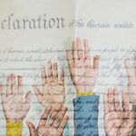 hands raised in from of US constitution