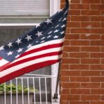 American flag hanging in front of a house