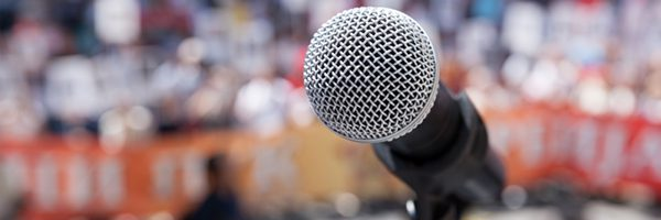microphone in front of unfocused crowd