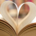 Book page in heart shape with library background