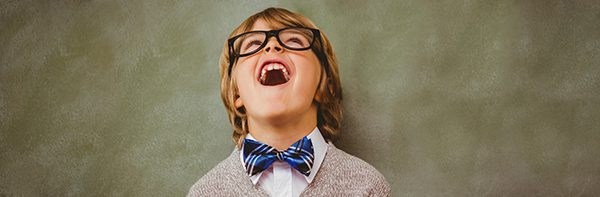 a young boy with blue bow-tie and glasses laughing with his head back