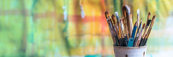 paint brushes in front of a painted canvas