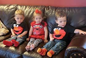 Triplets of Jennifer Navarette '08 sitting on a black leather couch