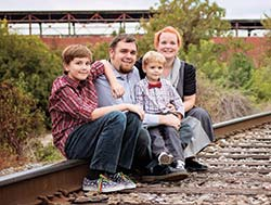 Meagan Hendrickson Hickey with her family sitting on railroad tracks