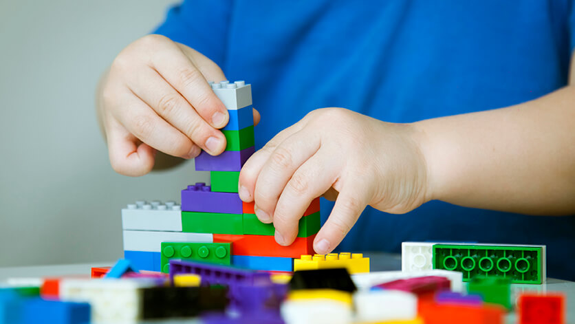 child hands building colorful legos
