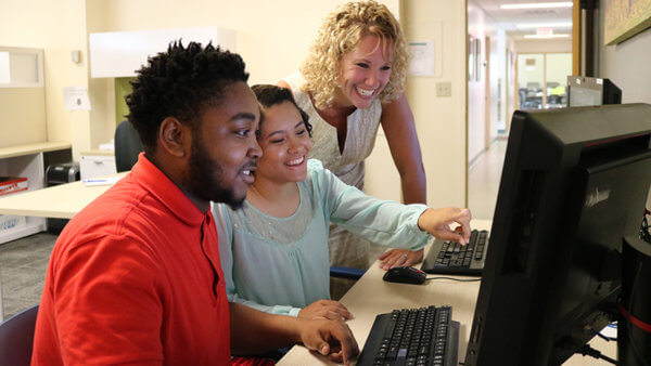 students smiling and laughing on a computer in the student support center