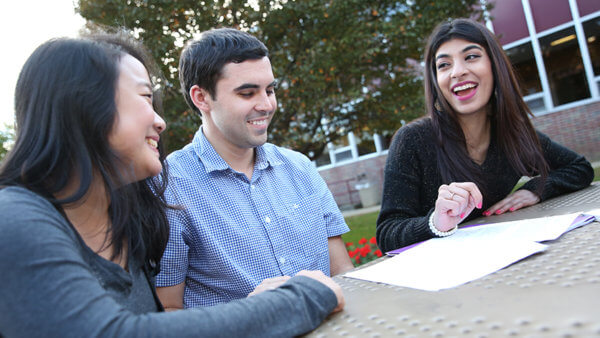 students laughing and studying at picnic table