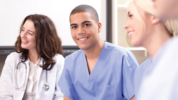 male nurse smiling with two female nurses