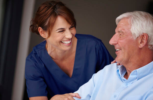 nurse smiling and helping an elderly man