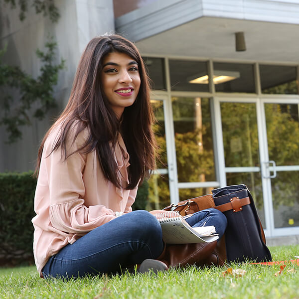 student sitting in grass in front of Main building with bag and books