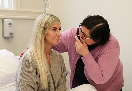 nursing student, Jill McLellan Phelps checks eyes of Tabitha Wright