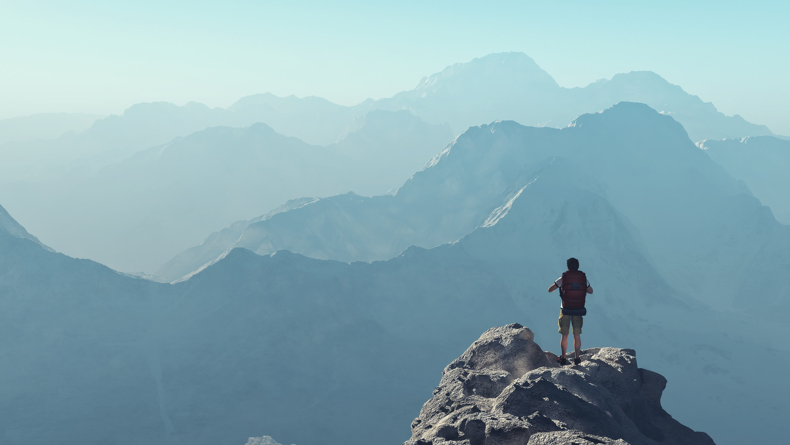 man on top of a mountain overlooking more vast mountains