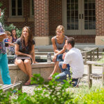 students sitting around courtyard fountain with books