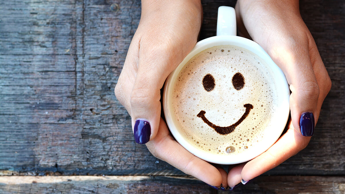 female hands holding coffee mug with smiling foam