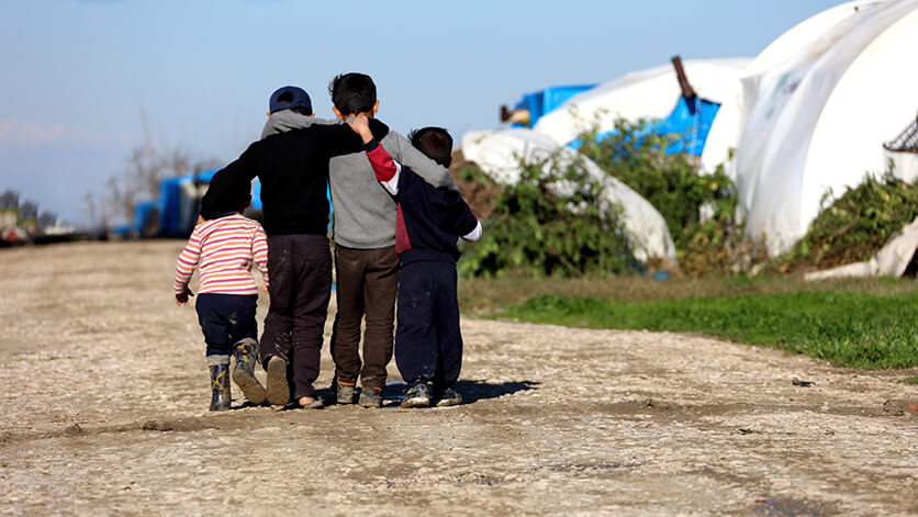 Four children walking away together arm and arm
