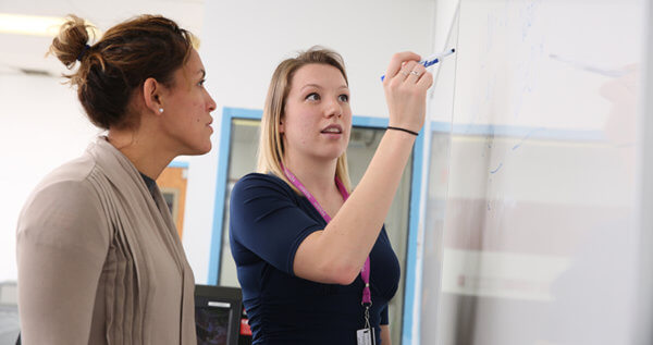 Student and Professor working out a problem on a whiteboard