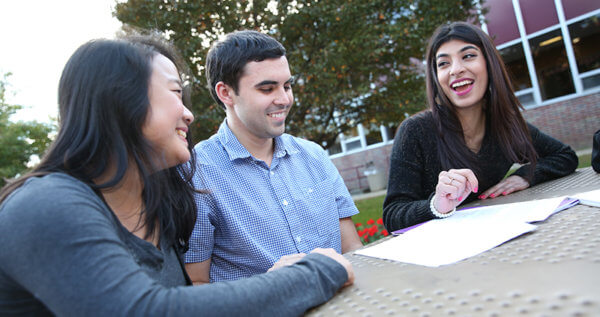 Three students sitting at a table outside