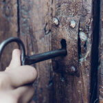 Someone opening a wooden door with a skeleton key