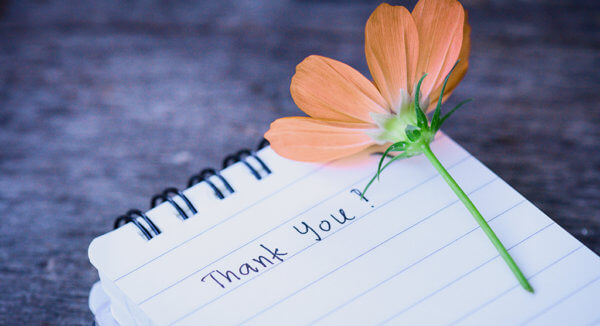 thank you written on a notepad with a flower