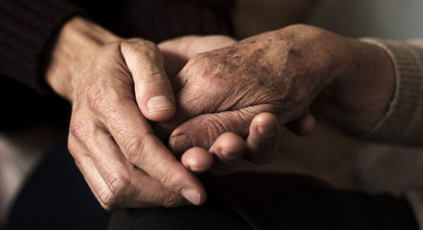 young adult hand holding the hand of an elderly person
