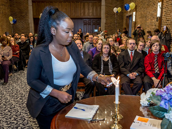 female student light a candle at the Phi Theta Kappa ceremony