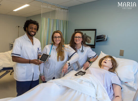 three nursing students in simulation lab next to manikin