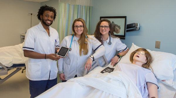 three nursing students in simulation lab next to manikin