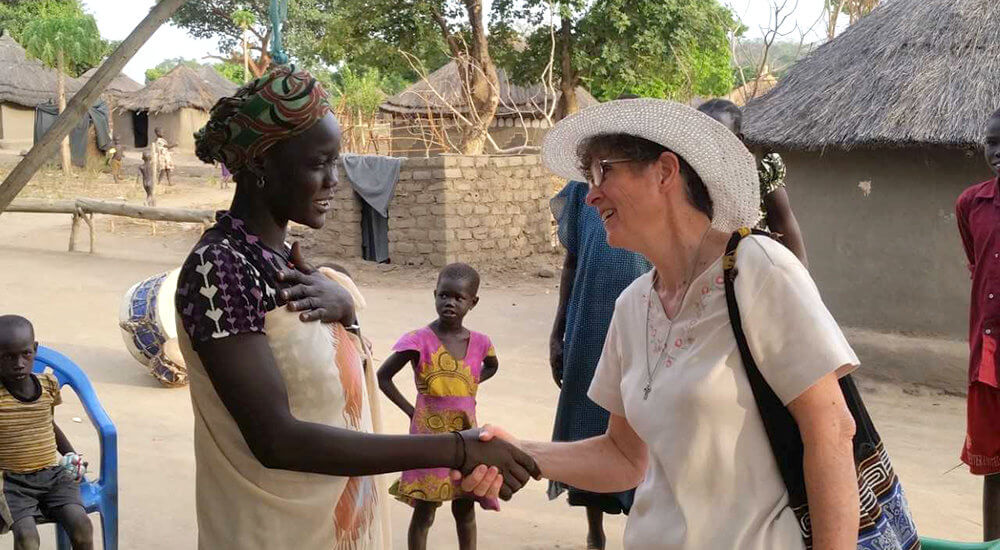 Marilyn Lacey shaking the hand of an African woman