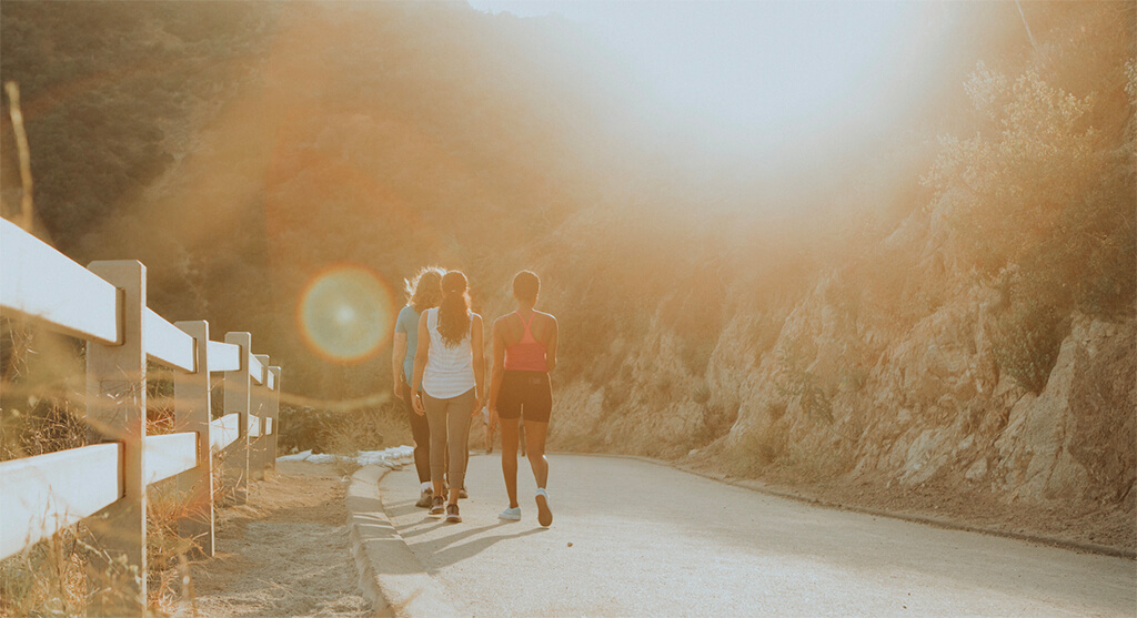 women walking down a road with sun shining on them