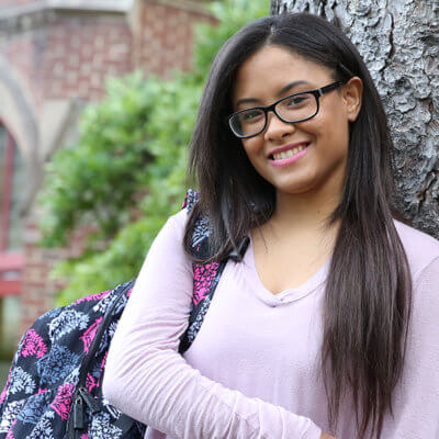 Smiling Student Leaning on Tree